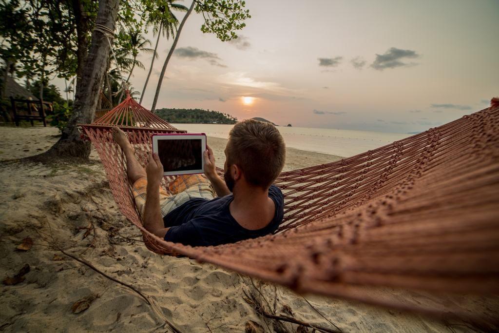 Mann mit Tablet in einer Hängematte