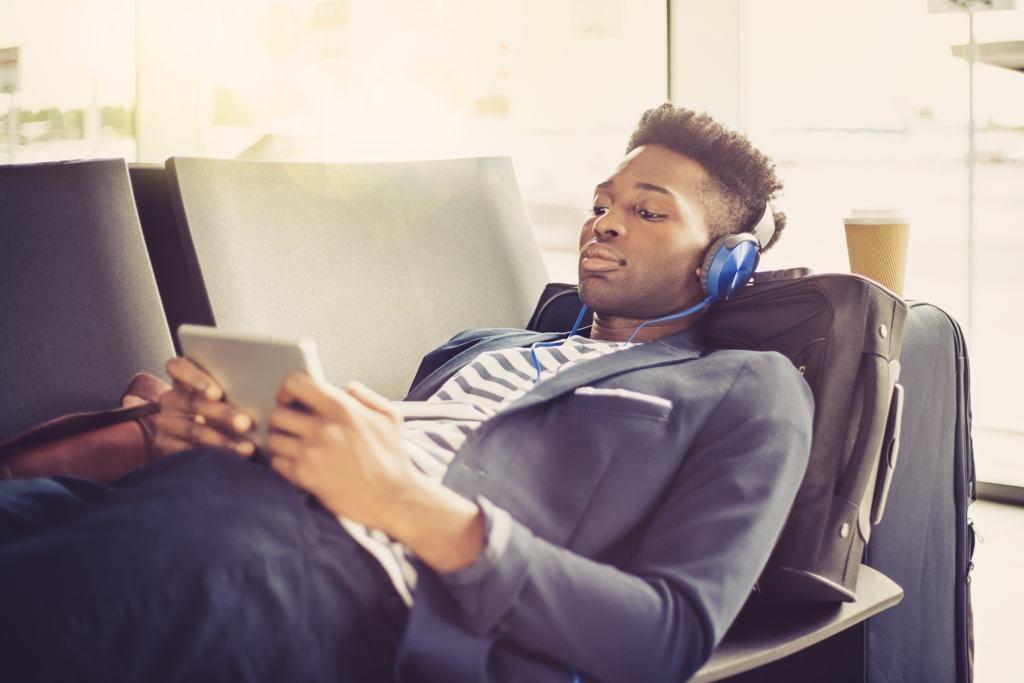 Mann mit Kopfhörer am Flughafen