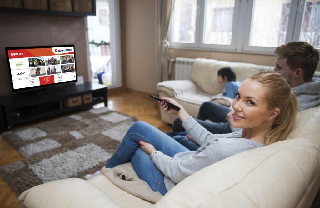 Familie sitzt auf Couch und schaut HD Austria
